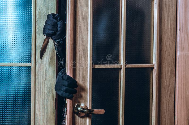 The criminal enters the house in the dark. Man`s hands in black gloves and a knife stock image