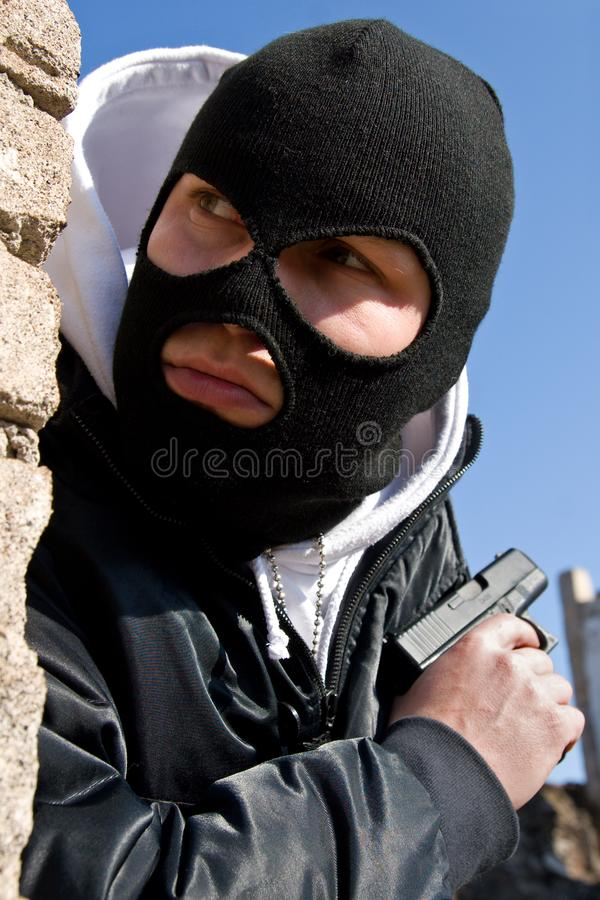 Criminal with a gun waiting for a victim stock image