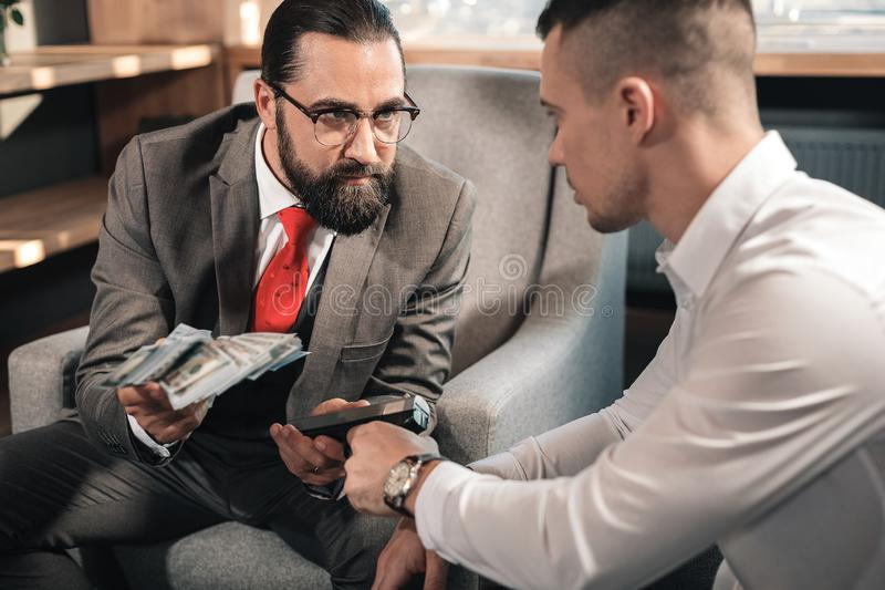 Criminal holding gun while demanding man to give him money stock image