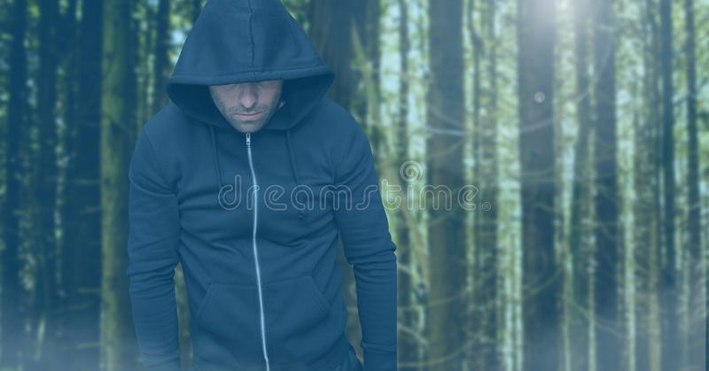 Criminal in hood in front of forest stock photography