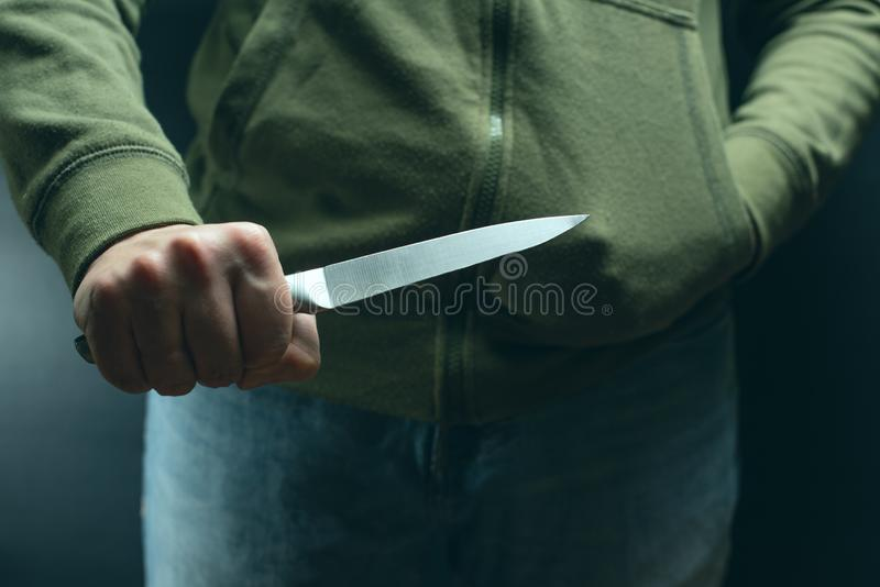 A criminal with a knife weapon threatens to kill. Criminality, crime, robbery thug stock photo