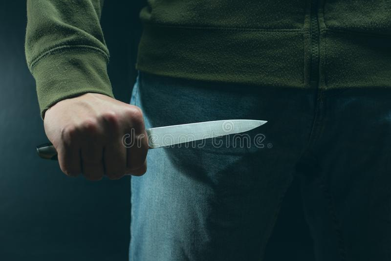 A criminal with a knife weapon threatens to kill. Criminality, crime, robbery thug royalty free stock image