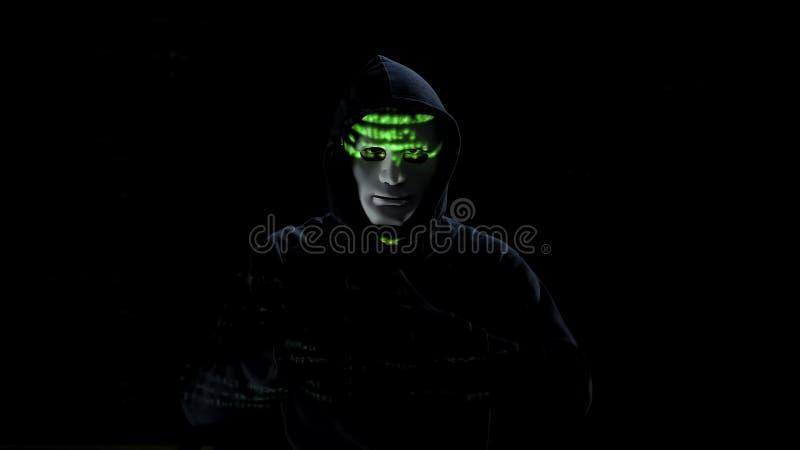 Criminal masculino en la máscara blanca que roba el banco, cortando el sistema de seguridad electrónico imagen de archivo
