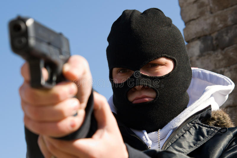 Criminal In Mask Aiming His Target Stock Photo