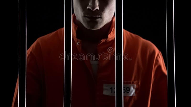 Criminal in orange uniform behind prison bars, serving life sentence for murder stock photos