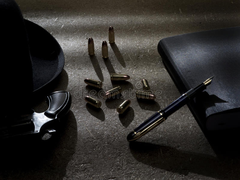 Criminal Scene. Table top set of a gangster or mobster's table. Including a gun or revolver, fedora, bullets, fountain pen, and ledger or notebook stock images