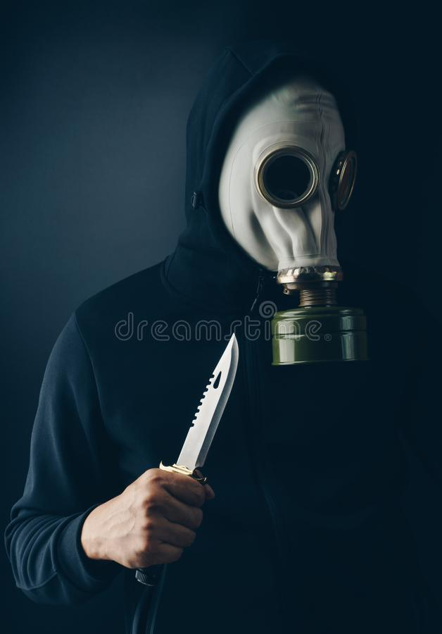 A scary thief in gas mask with a combat knife stock image