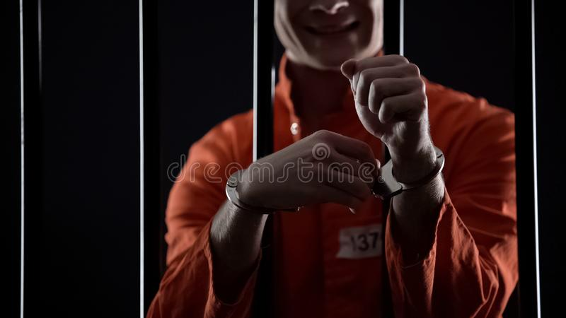 Criminal trying to unlock handcuffs, standing behind bars, escape from prison. Stock photo royalty free stock image