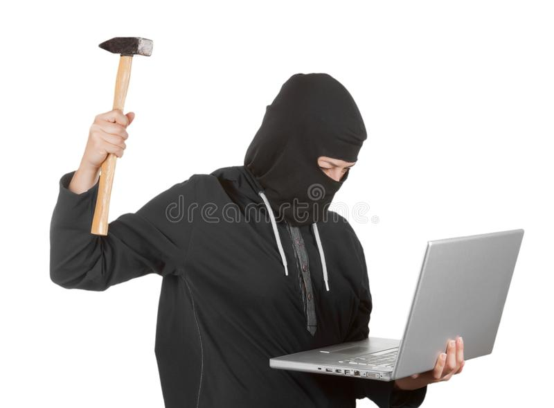 Criminal Woman Hacker Wearing Hood On in Black Clothes and Balaclava Destroy Laptop with Hammer royalty free stock photo