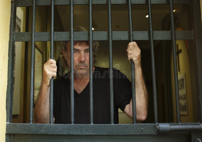 Criminale in prigione dietro le barre fotografie stock