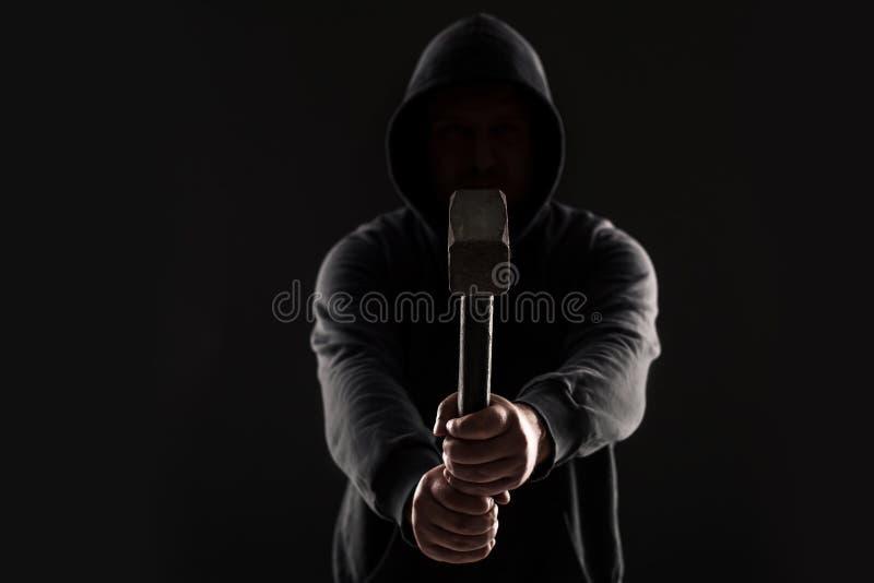 Criminale in vestiti e passamontagna scuri con il martello immagine stock