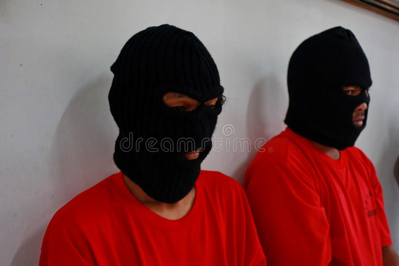 Criminali di cui le mani sono ammanettate, immagini stock