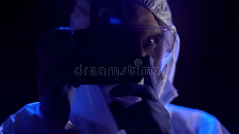 Criminalista que coge imágenes de las pruebas por la cámara en el cierre de la escena del crimen, trabajo fotografía de archivo