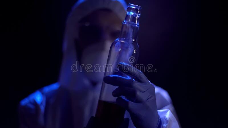 Criminalista que sostiene la botella de cristal en las manos, analizando pruebas de la escena del crimen fotografía de archivo libre de regalías