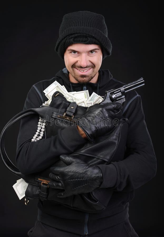 Criminality. Burglar with stolen goods. Angry burglar holding stolen goods while smiling against black background royalty free stock image