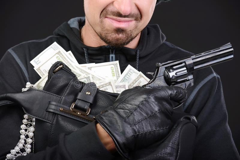Criminality. Burglar with stolen goods. Angry burglar holding stolen goods while smiling against black background stock photography