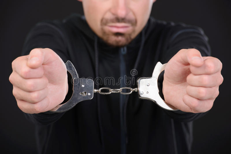 Criminality. Busted burglar. Angry burglar in handcuffs grimacing at camera while standing against black background stock image