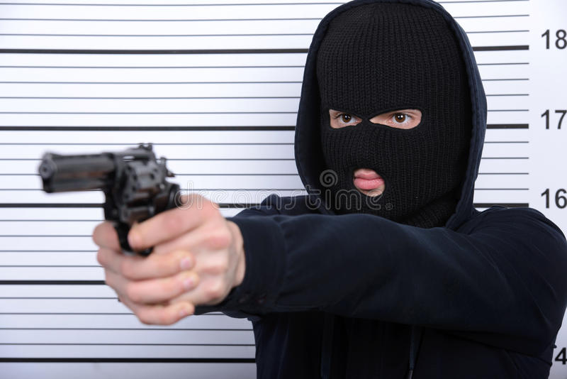 Criminality. Busted burglar. Angry burglar threatens arms standing against police line-up stock photos