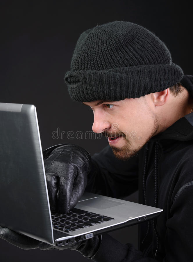 Criminality. Computer hacking. Close-up of frustrated criminal using computer stock photos