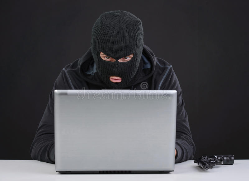 Criminality. Computer hacking. Close-up of frustrated criminal using computer royalty free stock photo