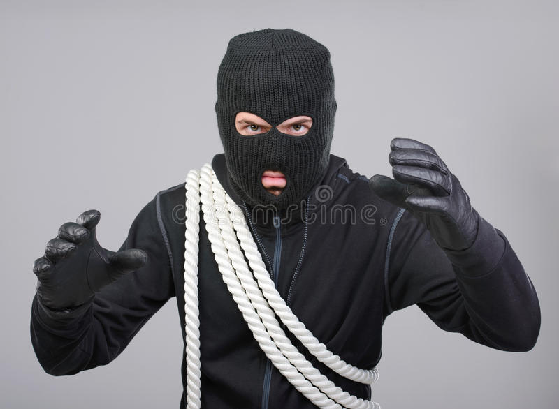 Criminality. Male offender from Balaklava in the head with a rope. Isolated on black background royalty free stock photo
