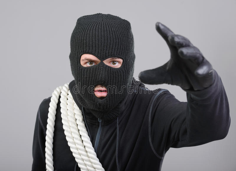 Criminality. Male offender from Balaklava in the head with a rope. Isolated on black background royalty free stock photos