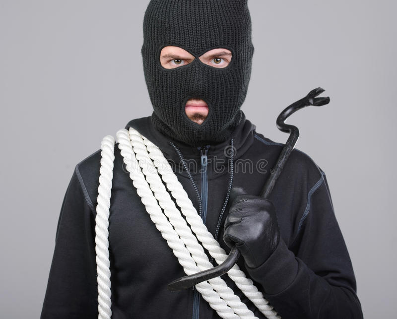 Criminality. Male offender from Balaklava in the head with a rope and scrap. Isolated on black background royalty free stock images