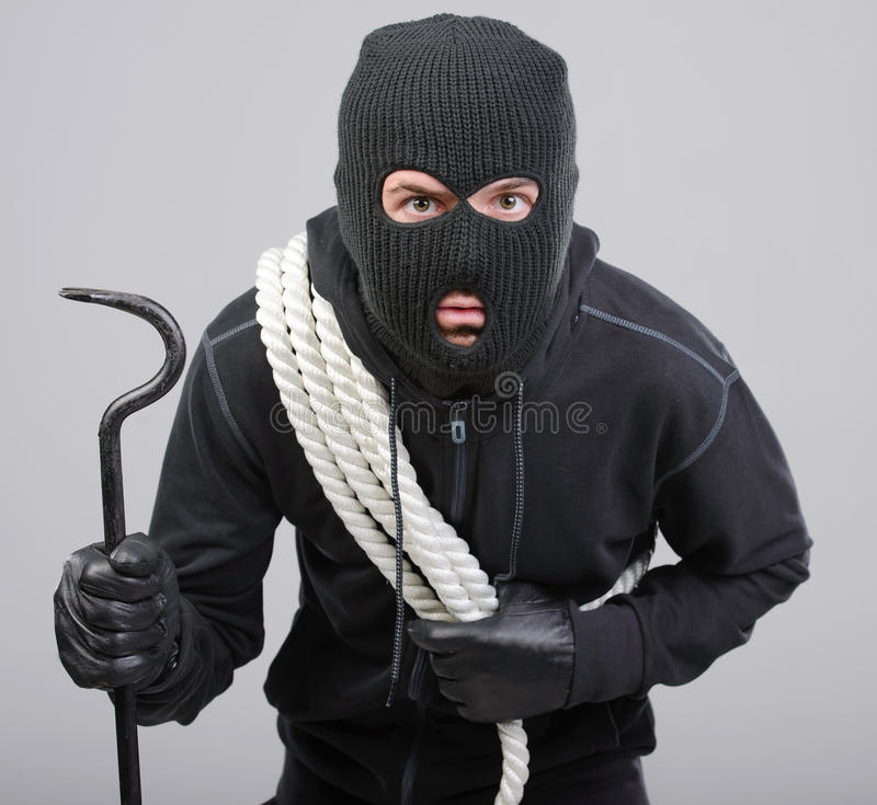 Criminality. Male offender from Balaklava in the head with a rope and scrap. Isolated on black background stock photography