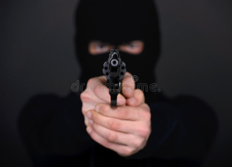 Criminality. Masked robber with gun aiming into the camera against a black background stock photo