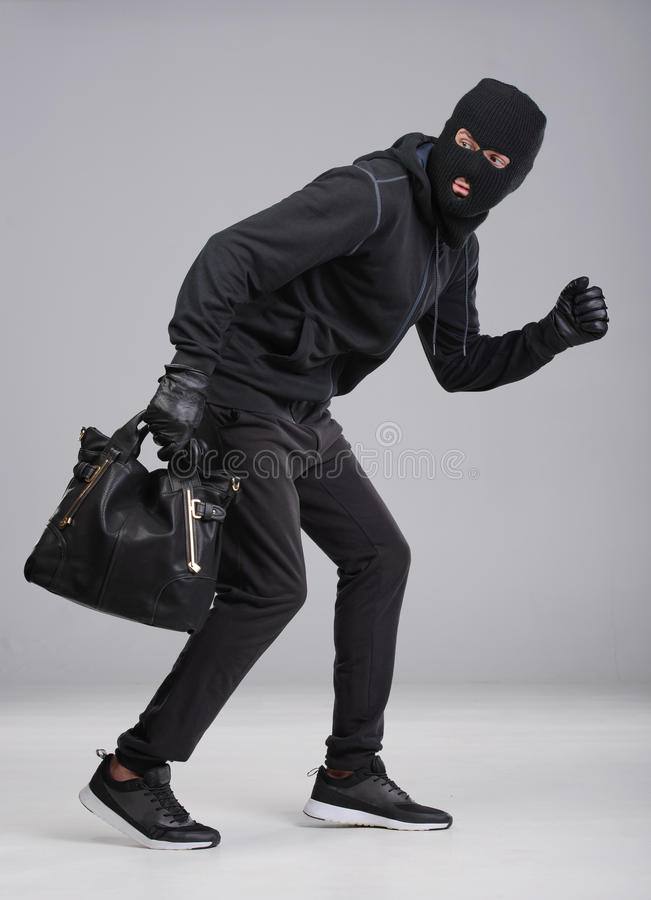 Criminality. Portrait of running male burglar with a handbag. Isolated on gray background stock photo