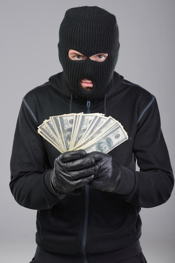 Criminality. Robber in a mask rejoice stolen money. Gray background stock images