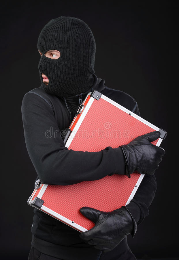 Criminality. Stealing a suitcase. Frustrated thief in black balaclava holding a stolen suitcase while isolated on black royalty free stock image