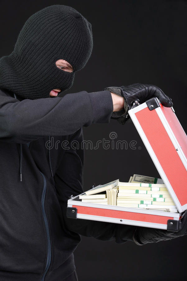 Criminality. Stealing a suitcase. Frustrated thief in black balaclava holding a stolen suitcase while isolated on black stock photos