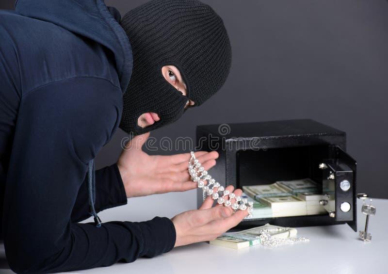 Criminality. Thief burglar stealing money during home safe codebreaking stock image