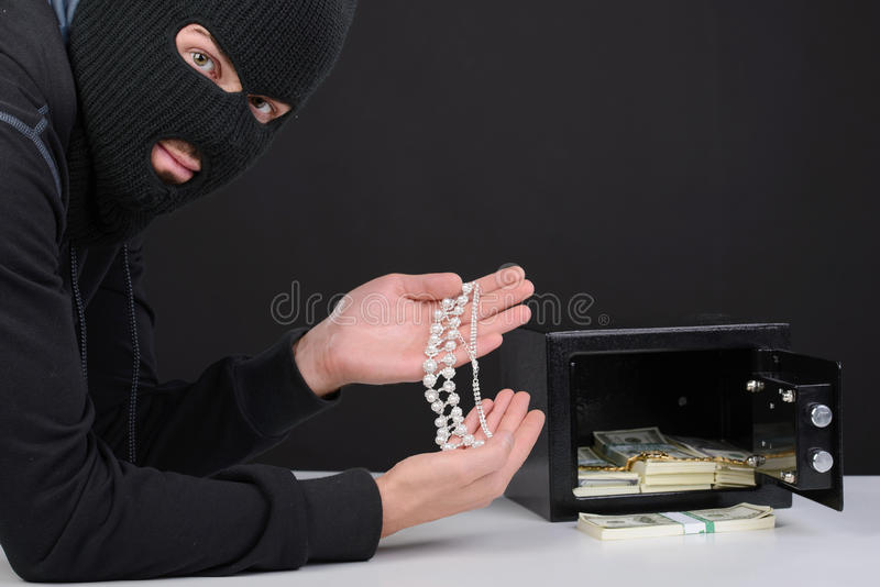 Criminality. Thief burglar stealing money during home safe codebreaking stock photography