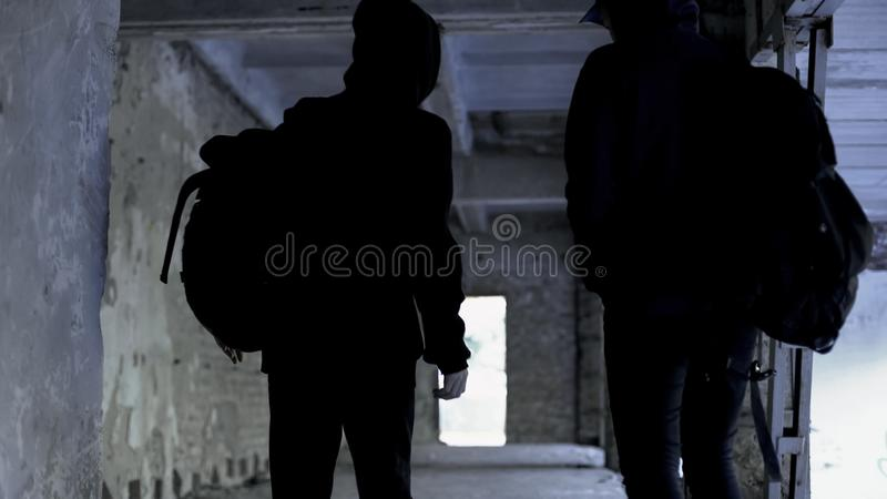 Criminals wearing black walking in abandoned house, crime planning, conspiracy. Stock photo stock photography