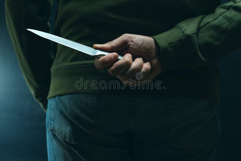 Criminel avec l'arme de couteau cachée derrière le sien de retour photos libres de droits
