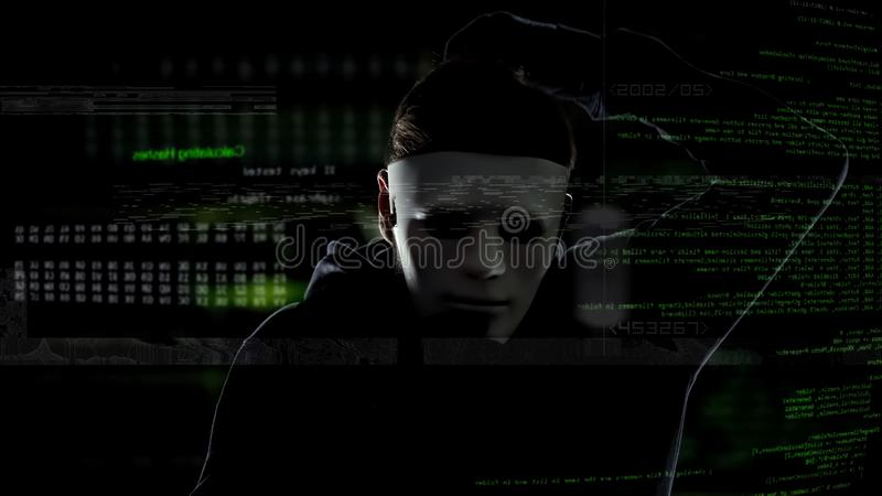 Criminel de Cyber dans le masque blanc entaillant le système de sécurité, activités illégales, attaque image stock