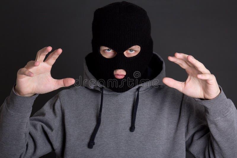 Criminel fâché d'homme dans le masque noir au-dessus du gris photographie stock