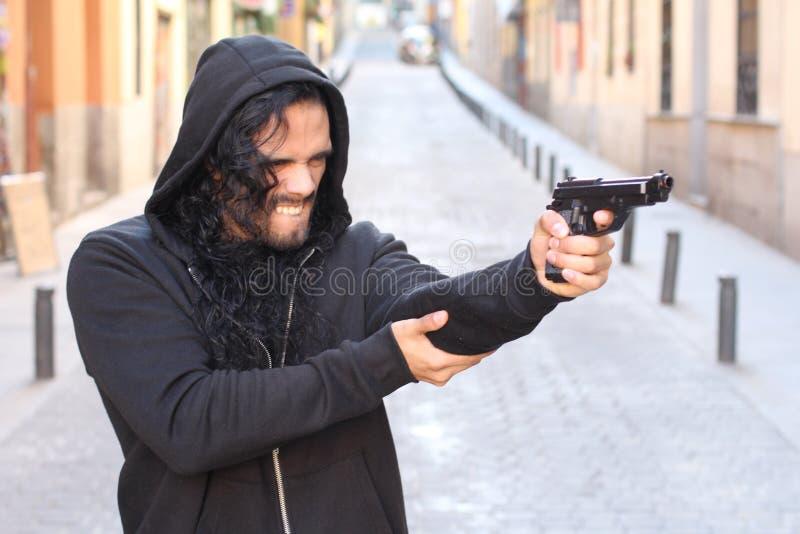Criminel f?ch? tenant une arme ? feu dehors photographie stock