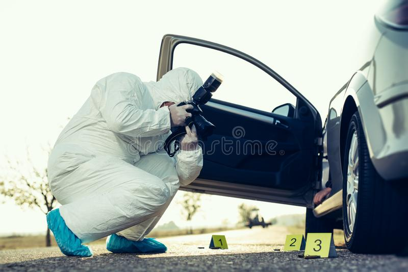 Criminological expert collecting evidence at the crime scene. stock photos