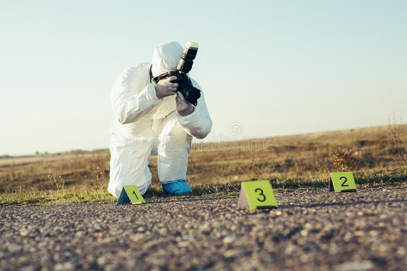 Criminological expert collecting evidence at the crime scene. stock image