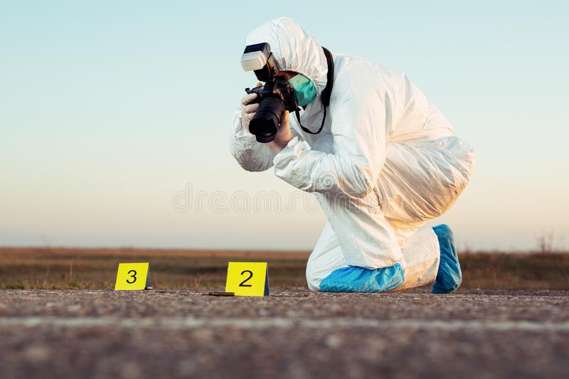 Criminological expert collecting evidence at the crime scene. Young Criminological expert collecting evidence at the crime scene stock photo