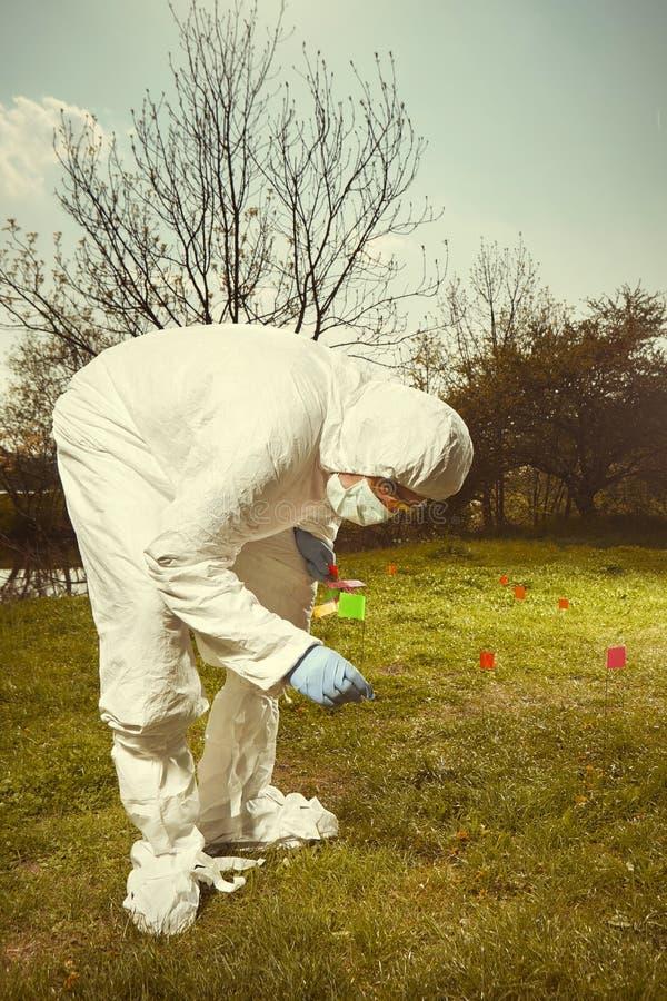 Criminoloogtechnicus in het steriele beschermende algemene werken van DNA bij het vinden van bewijsmateriaal in terrein met vlagg royalty-vrije stock afbeeldingen