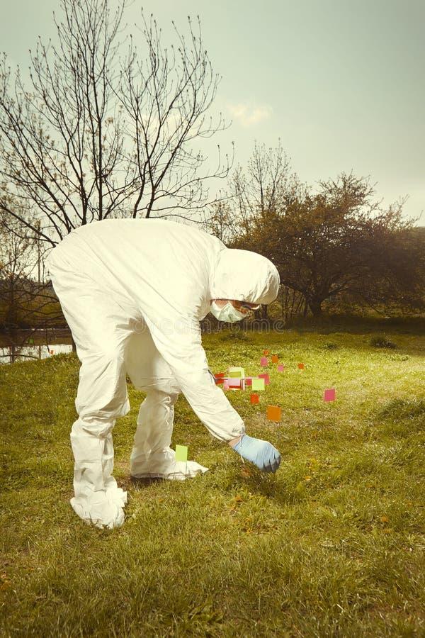 Criminoloogtechnicus in het steriele beschermende algemene werken van DNA bij het vinden van bewijsmateriaal in terrein met vlagg stock foto's