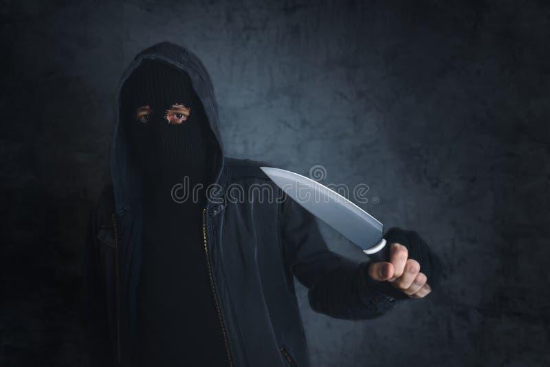 Criminoso com a faca afiada que threating, o ponto de vista da vítima imagens de stock royalty free