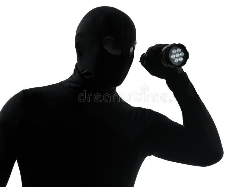 Criminoso do ladrão com silhueta da lanterna elétrica fotografia de stock