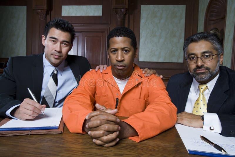 Criminoso e advogados que sentam-se na sala do tribunal fotografia de stock