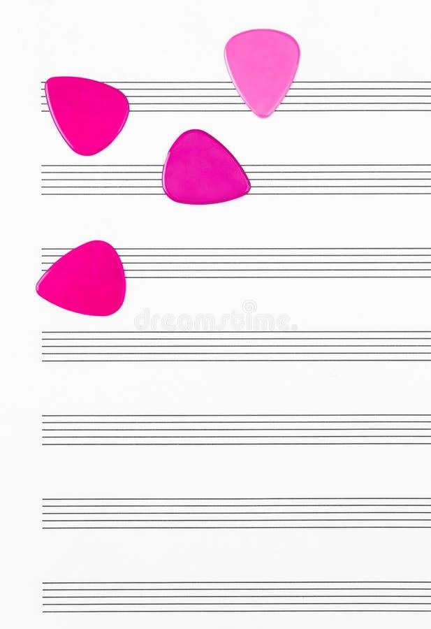 Crimson guitar picks on empty sheet music paper royalty free stock photos