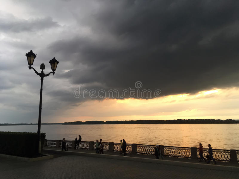 Crimson orange sunset on the river, dark clouds over the city`s waterfront.  stock images